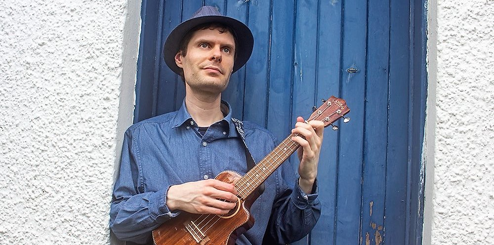 Mike Haysom holding ukulele against blue door